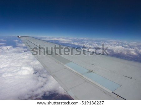 View of the white fluffy cumulus clouds flying from Broome, North Western Australia to Perth with the wing of the plane  in view on a cloudy afternoon in summer Wet Season is beautifully exhilarating.