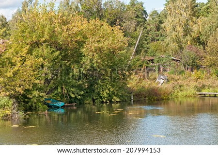 View on riverside with growth on bank and moored wooden boat under tree. Nikolo-Uryupino village, Moscow region, Russia.