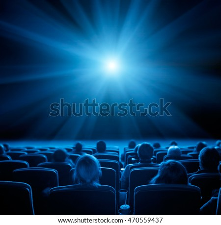 viewers watch film at movie theatre, long exposure, blue glow