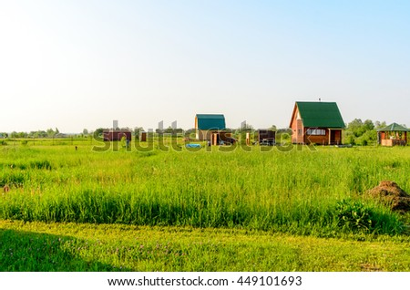 Village house in a green field during the day.