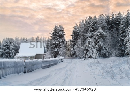 Village is in northern woods of Karelia, winter road with wooden house at evening. Russia