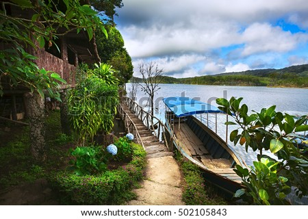 Village wooden house and bridge near a mountain lake in the forest. On the water there at the dock the boat is blue.