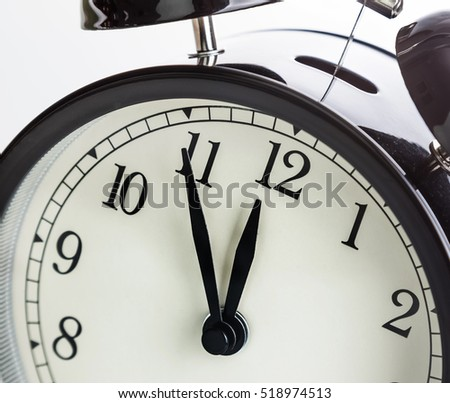 vintage alarm clock is showing midday or midnight. It is twelve o'clock, holiday happy new year festive or lunch concept on white background