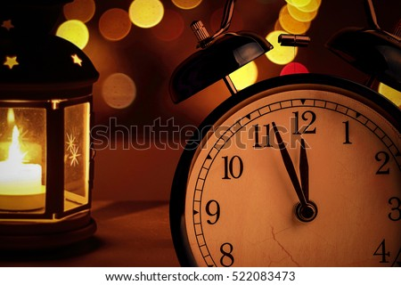 vintage alarm clock is showing midnight. It is twelve o'clock, christmas and bokeh, holiday happy new year festive concept on light lantern background