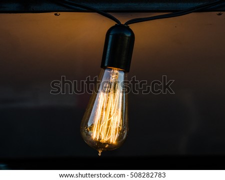 Vintage antique hanging light bulb at a street food market. Holidays and business good idea concept.