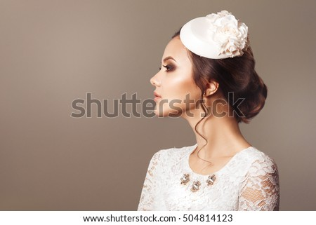 Vintage beauty portrait of a cute brunette bride in a decorative hat isolated in profile.