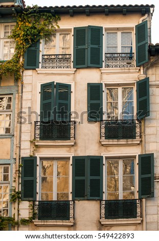 Vintage building facade wall of a french building in modern style with colorful windows  in French town Bayonne in sunset light.