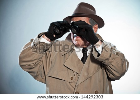 Vintage detective with mustache and hat. Looking through binoculars. Studio shot.