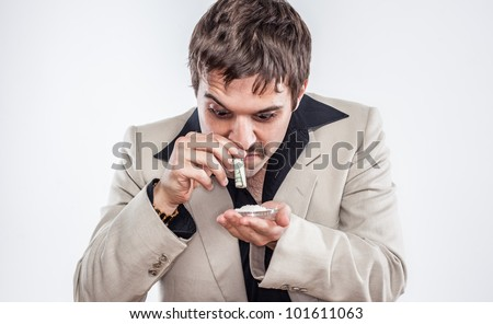 Vintage drug addict sniffing cocaine or heroine in 1970's suit using dollar bill