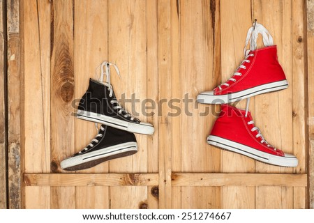 Vintage hanging shoes tied on wooden background