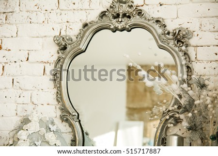 Vintage interior with a mirror in a beautiful frame and artificial flowers. Background for a card
