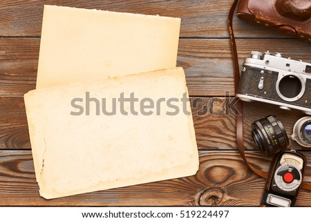 Vintage old 35mm cameras, lenses and light meter on wooden background
