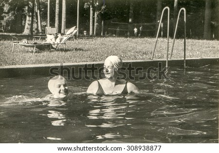 Vintage photo of mother and daughter bathing in swimming pool, 1950's