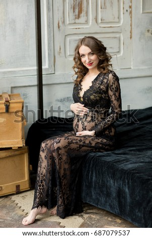 vintage pregnant woman in black lace dress and hat on bed