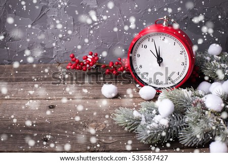 Vintage red clock, Santa hat ,  branches fur tree and red berries on aged  wooden background. Selective focus. Place for text. Drawn snow.