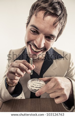Vintage 1970's drug user doing coke looking high with rolled up dollar bill on plastic dish