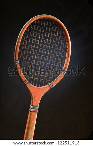 Vintage tennis racket over dark background