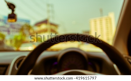 vintage tone blur image of people driving car on day time for background usage. (take photo from inside)