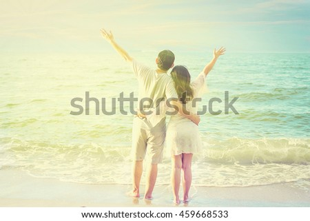 Vintage tone photo of Asian couple on beach with warm sun light from top corner
