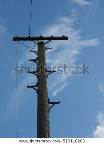 Vintage wooden telegraph pole over the blue sky