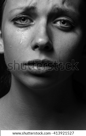 Violence and abuse of girls theme: portrait of a beautiful young girl with tears in her eyes, sad woman in the studio shot black and white photo