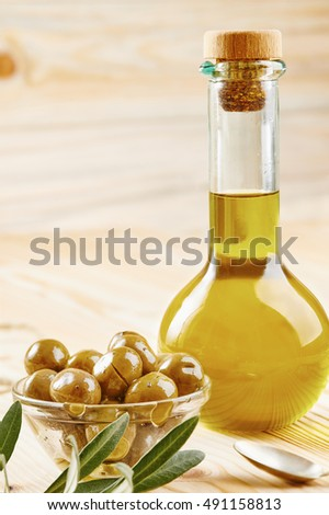Virgin olive oil, olives in glass bowl, spoon and olive branch on wooden table