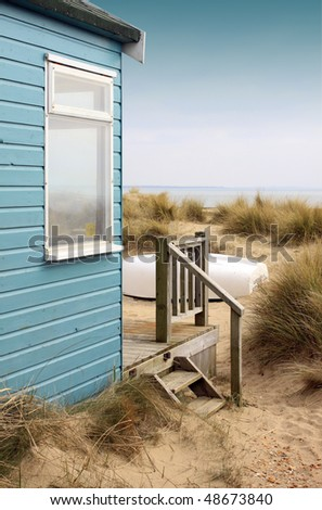 Viw of the side of a blue wooden beach hut with wooden terrace, looking towards the coast/beach. A white upturned boat rests in front of the hut amongst the sand and reed bushes.