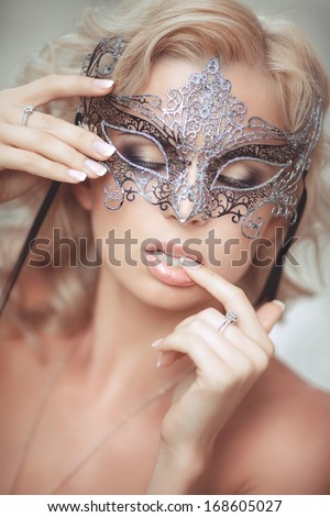 vogue style portrait of beautiful delicate woman in venetian mask and fashionable dress. Sexy woman in evening dress and carnival mask outdoors. soft focus.