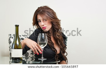 Vogue style vintage portrait of a sexy woman with black stocking sitting on chair .White vine in a bottle on table