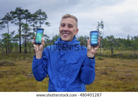 Voiste, Estonia - August 13, 2016: Young man smiles happily standing in a rural landscape with two smartphones showing Pokemon Go display. Pokemon Go is a smartphone game with spiking popularity.