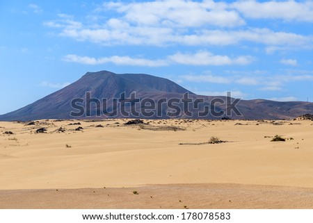 Volcanic mountains in desert landscape of sand dunes in Corralejo National Park, Fuerteventura, Canary Islands, Spain