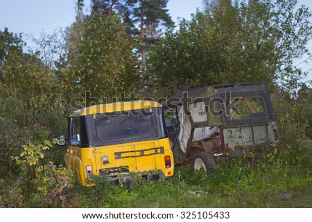 VYBORG, RUSSIA - OCTOBER 3, 2015: Old broken off-road cars UAZ are in green thickets, villas Kirov, Vyborg, Russia
