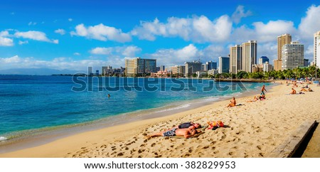 Waikiki Beach, Honolulu, Hawaii, USA - Dec 11, 2015: Sun-bathers and beach-goers love the tropical weather to relax and enjoy the cool water. Hotels and apartments dot the skyline in the distance.