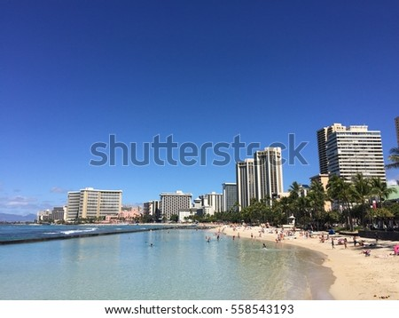 Waikiki beach with people at the beach and hotels in the background.