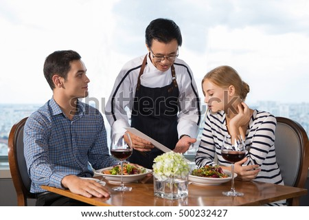 Waiter Offering Couple Main Courses in Restaurant