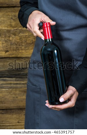 waitress opening red wine bottle, gray apron