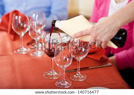 waitress pouring red wine at guest�´s glasses