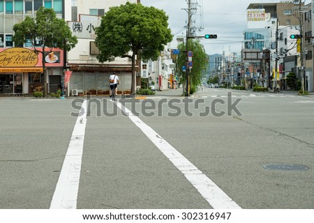 WAKAYAMA, JAPAN - JULY 19, 2015: Crosswalk and Bicycle in Wakayama street.