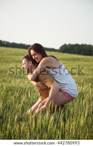 Walk a happy young couple on the nature outside the city. The guy carries the girl on sunset wheat field