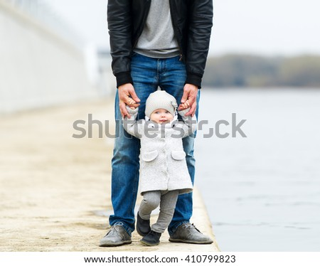 Walk in city park. The father holds the little daughter by hands.