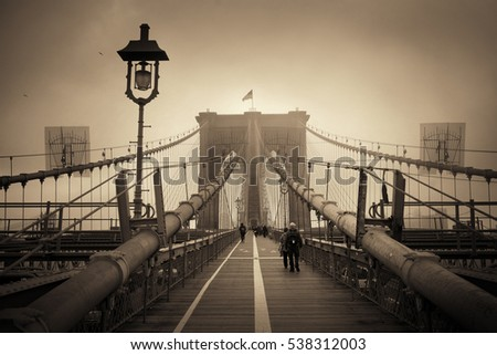 Walk on Brooklyn Bridge in a foggy day in downtown Manhattan New York City.