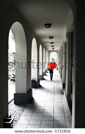 walking girl under red umbrella