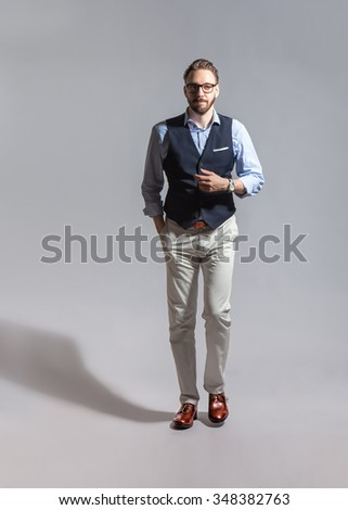 Walking suave handsome stylish bearded man with glasses in classic vest