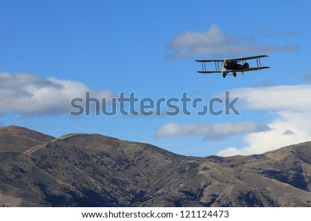 "WANAKA MARCH 03: Bristol F.2B vintage aircraft flies over the mountains during the royal New Zealand air force 75th anniversary""Warbirds Over Wanaka"" airshow on March 03, 2012 in Wanaka New Zealand"