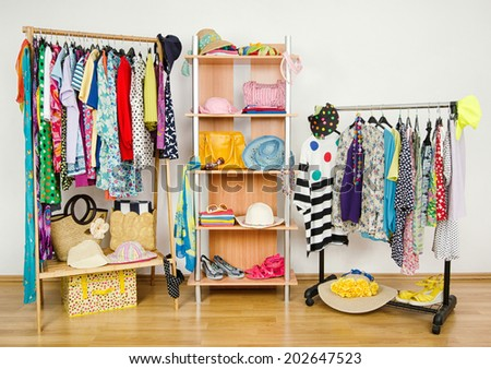 Wardrobe with summer clothes nicely arranged. Dressing closet with colorful clothes and accessories on hangers and a shelf.