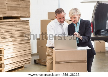 Warehouse manager and colleague using laptop