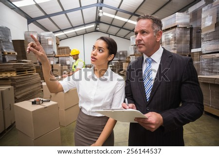 Warehouse manager showing something to her boss in a large warehouse