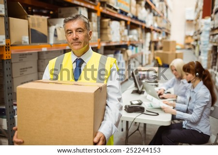Warehouse manager smiling at camera carrying a box in a large warehouse