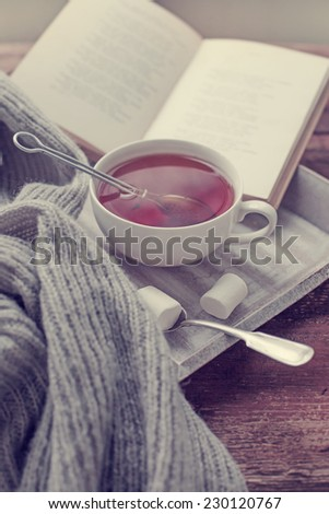 Warm knitted sweater,cup of hot tea and  book on a wooden tray