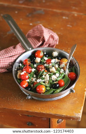Warm salad with french beans, cherry tomatoes, black olives, feta cheese and wheat croutons in a pan